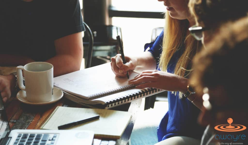 Hands of a Group of Business Workers Around a Table with Notebooks and Pens